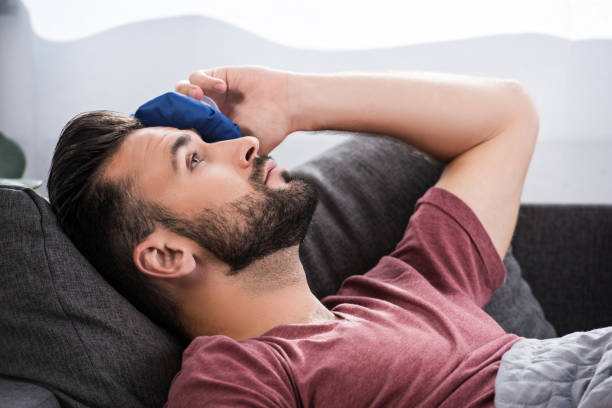 close-up portrait of sick young man lying on couch and holding ice pack on forehead - crioterapia foto e immagini stock
