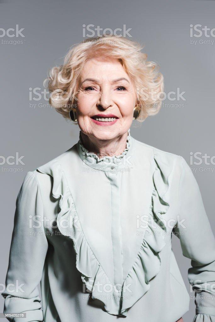 close-up portrait of smiling senior woman isolated on grey zbiór zdjęć royalty-free