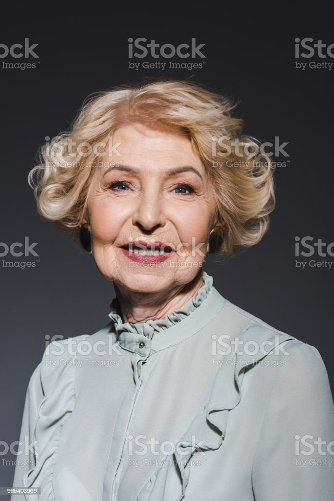 close-up portrait of smiling senior woman looking at camera on dark grey zbiór zdjęć royalty-free