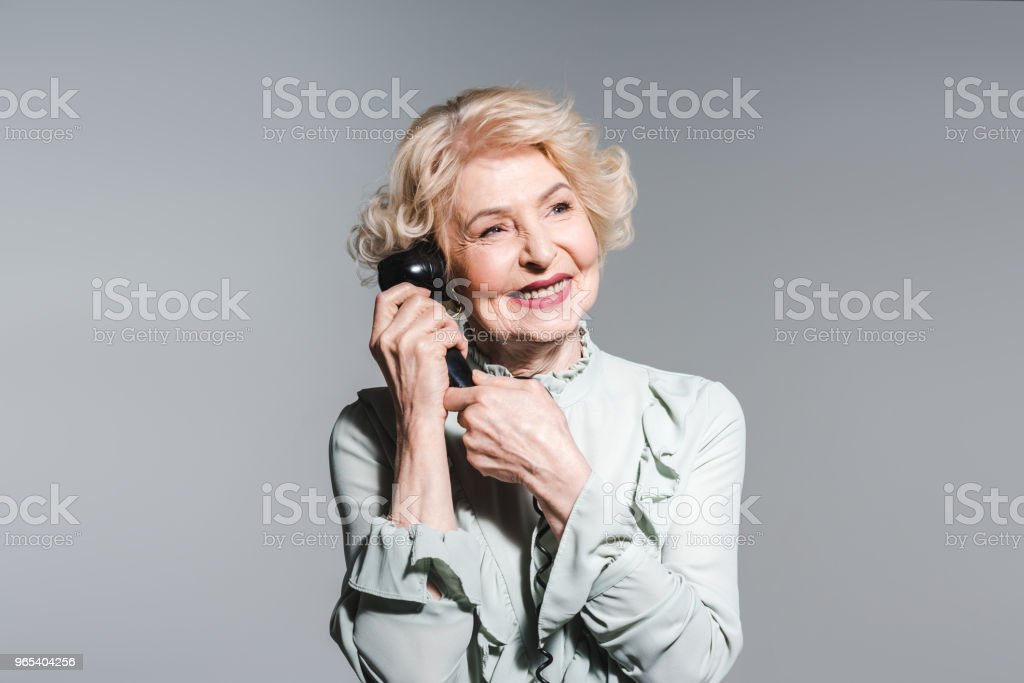 close-up portrait of smiling senior woman talking by vintage phone isolated on grey royalty-free stock photo