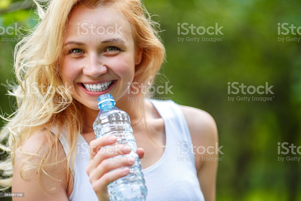 Closeup portrait of smiling woman with water bottle stock photo