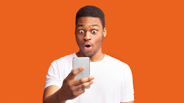 Closeup portrait of surprised african guy looking at phone Shocking News. Anxious black man looking at phone seeing bad news or photos over orange background, panorama gasping stock pictures, royalty-free photos & images