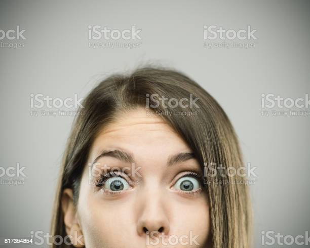 Close-up portrait of surprised beautiful young woman with excited expression. Real people female is against gray background. She has long brown hair. Horizontal studio photography from a DSLR camera. Sharp focus on eyes.