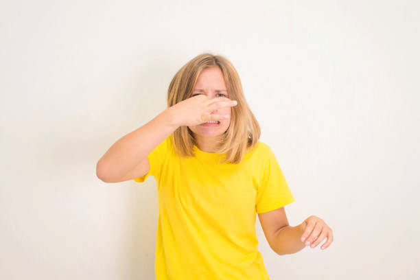 Closeup-Porträt von Teenager-Mädchen kneift Nase mit Fingern Hände sieht mit Ekel etwas stinkt schlechten Geruch isoliert auf weißen Wandhintergrund mit Copyspace. Menschliche Gesichtsausdruck Körpersprache Reaktion. – Foto