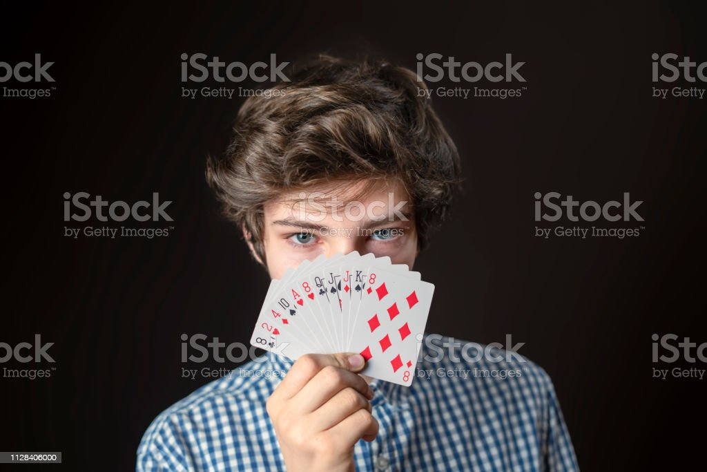 closeup portrait of teen male hold gambling card show it and cover...