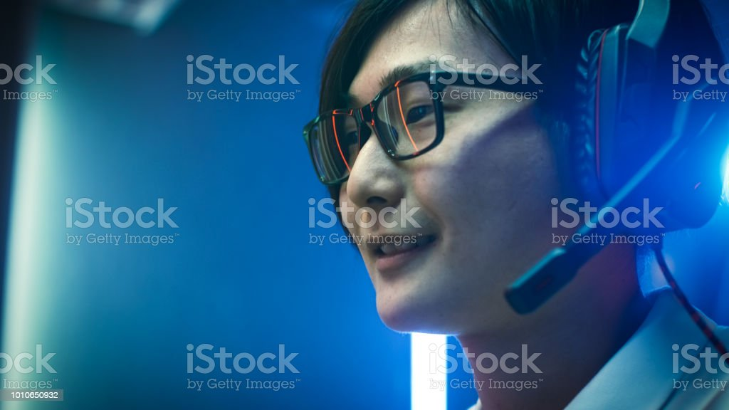 Close-up Portrait of the Professional Asian Gamer Playing in Online Video Game, He's wearing Glasses, talks/ chats with His Teammates / Friends through Headphones. Neon Colored Room. eSport Cyber Games Internet Championship Event. stock photo