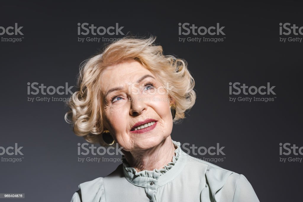 close-up portrait of thoughtful senior woman looking up on dark grey royalty-free stock photo