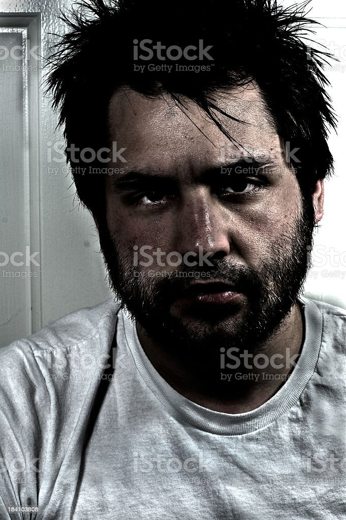 A close-up portrait of tired man's disheveled face and hair royalty-free stock photo