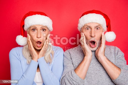 661896674istockphoto Close-up portrait of two shocked impressed people grey-haired married spouses husband wife granny granddaddy with opened mouth gesture palms to cheeks isolated over red pink background 1054298586