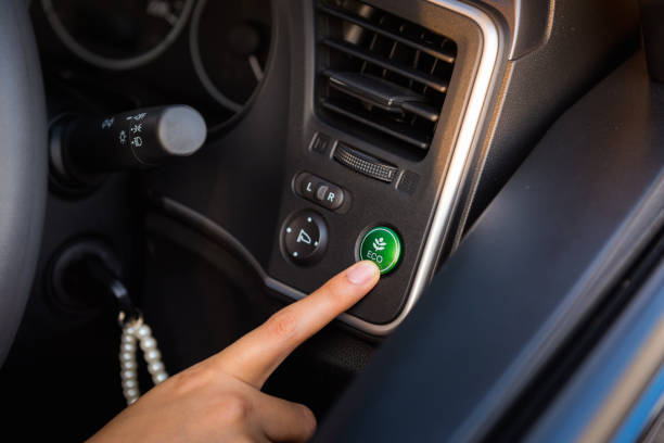 Close-up portrait of woman finger pressing switch on/off of eco mode in the car Close-up portrait of woman finger pressing switch on/off of eco mode in the car. hybrid car stock pictures, royalty-free photos & images