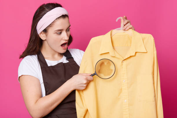 Closeup portrait of woman holds magnifier and shirt with spot in hand. Attractive lady wears white shirt and brown apron looks surprised, stands with opened eyes. Copy space for your advertisment. Closeup portrait of woman holds magnifier and shirt with spot in hand. Attractive lady wears white shirt and brown apron looks surprised, stands with opened eyes. Copy space for your advertisment. wet clothing women t shirt stock pictures, royalty-free photos & images