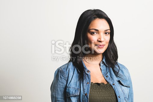 Portrait of mid adult woman smiling. Confident female is over white background. She is wearing smart casuals.