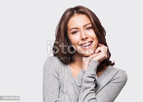 istock Close-up portrait of woman touching her face 626458256