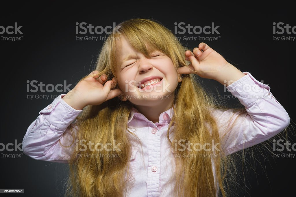 Closeup portrait of worried girl covering her ears, observing. Hear stock photo