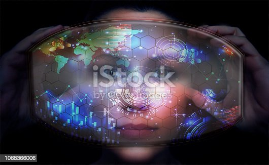 Close-up portrait of young and beautiful woman with the virtual futuristic glasses ( technology concept).Virtual holographic interface and young woman wearing glasses