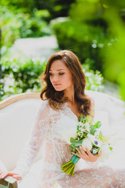 Close-up portrait of young beautiful bride in white negligee with bridal bouquet stock photo