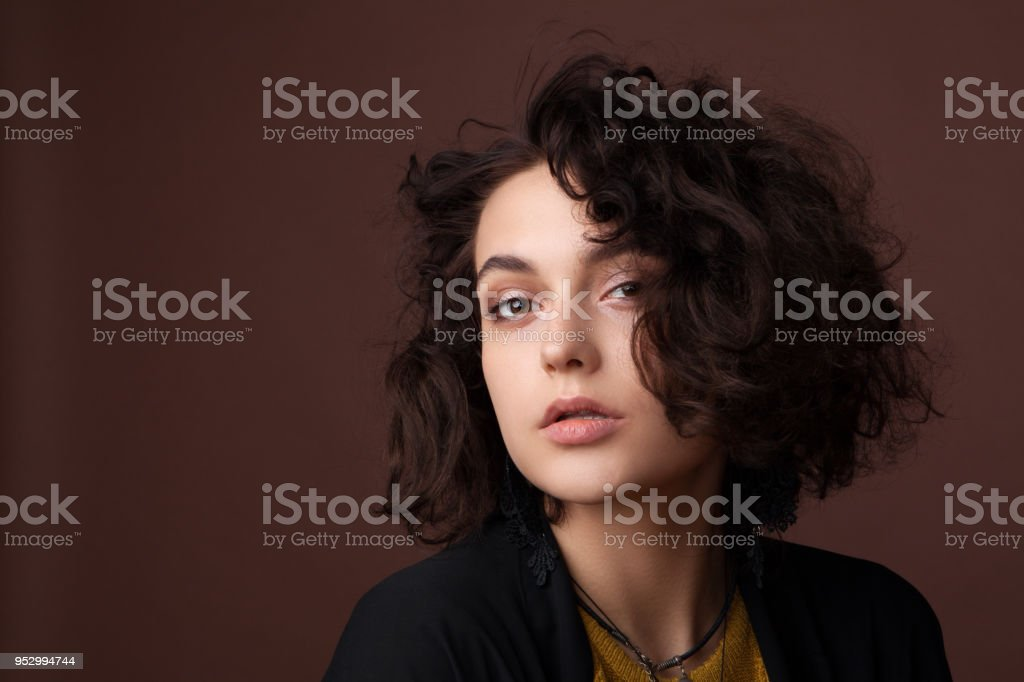 Close-up portrait of young beautiful girl in studio on brown background stock photo