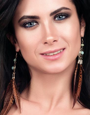 closeup portrait of young beautiful woman dark hair blue