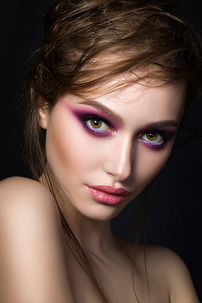 closeup portrait of young beautiful woman with bright pink smoke - lila augen make up stock-fotos und bilder