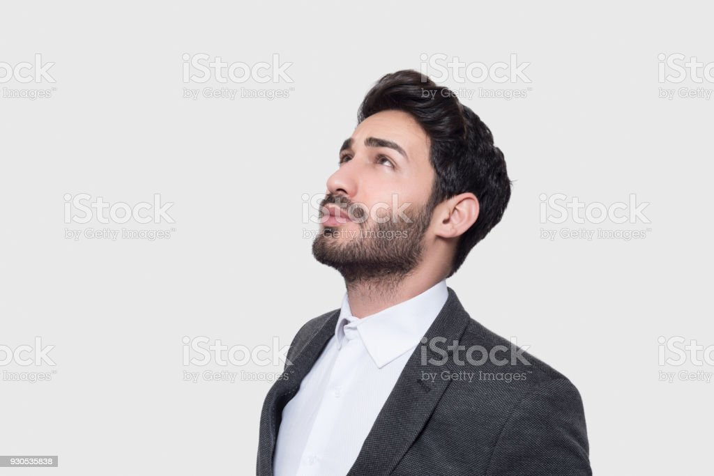 Close-up portrait of young businessman looking up over gray background stock photo