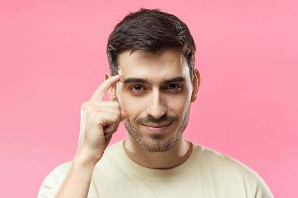 Closeup portrait of young European Caucasian man pictured isolated on pink background pressing finger to temple as if making viewer think more about offer or analyze information better for their good Closeup portrait of young European Caucasian man pictured isolated on pink background pressing finger to temple as if making viewer think more about offer or analyze information better for their good intelligence stock pictures, royalty-free photos & images