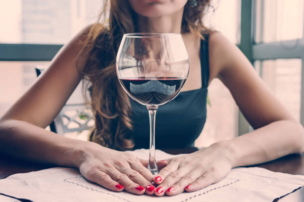 Closeup portrait of young female customer drinking red wine with eyes closed. Woman drinking wine, taking a SIP from a glass glass. Wine tasting in restaurant. stock photo