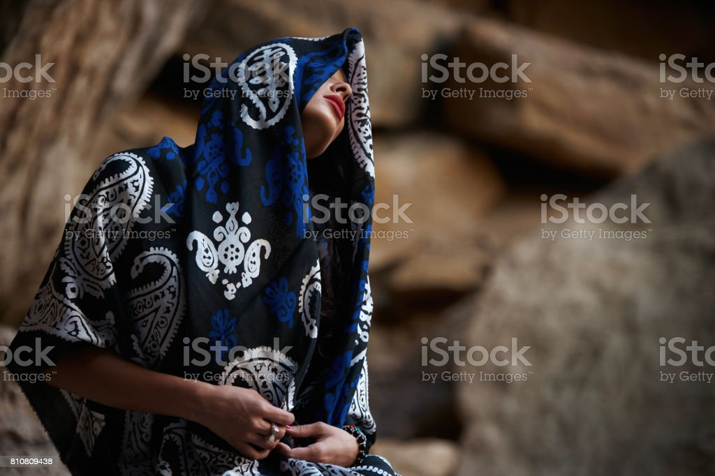 Close-up portrait of young female fashion model with colorfull silk scarf twisted round the head on abstract mountain background stock photo