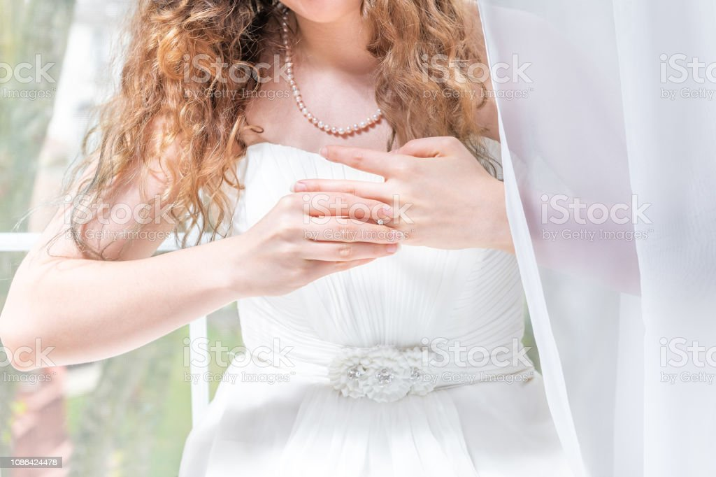 Closeup portrait of young female person, woman, bride in wedding dress, pearl necklace, standing by window, white curtains, taking off engagement diamond ring from finger with hands stock photo