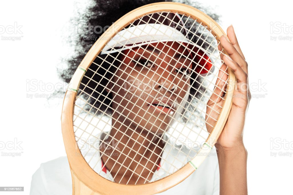 close-up portrait of young female tennis player holding racket in front of face isolated on white stock photo