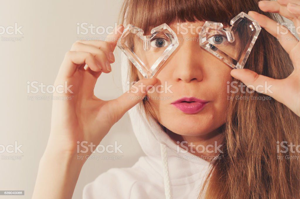 Closeup portrait of young girl in the hood looking through stock photo