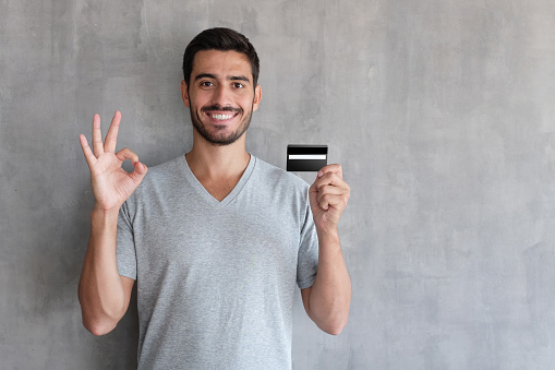 Closeup portrait of young handsome Caucasian guy pictured isolated on gray background, smiling, showing ok sign with his hand while holding debit or credit card in another one, feeling satisfied