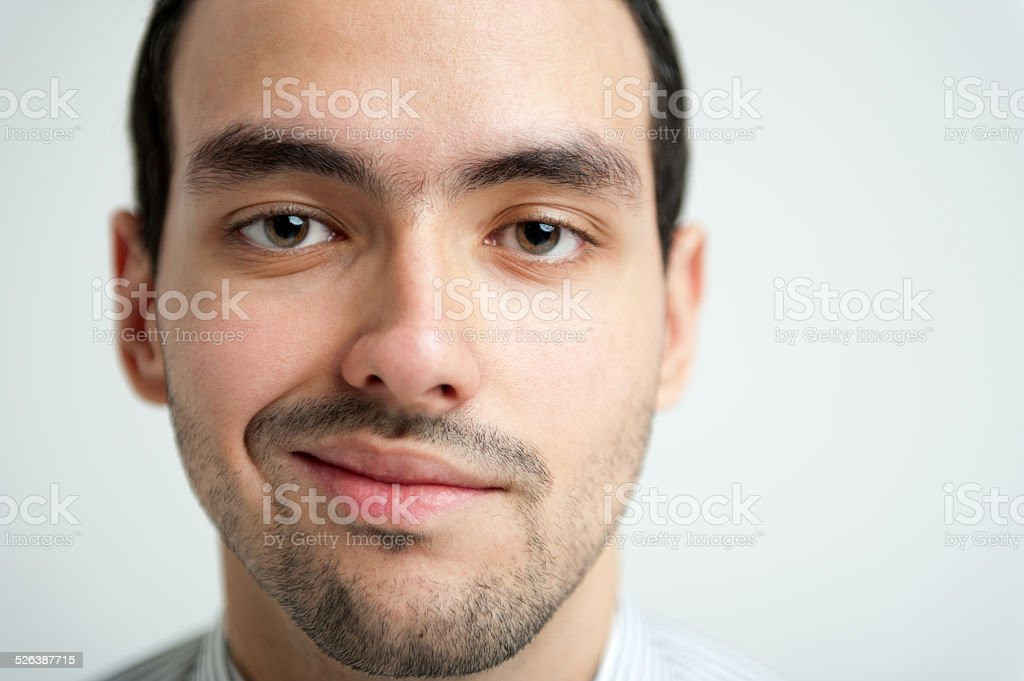 Close-up Portrait of young smiling brunet man stock photo