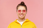 istock Close-up portrait of young smiling girl wearing yellow casual hoodie and round colored eyeglasses, hair tied in bun, isolated on pink background 1249362074