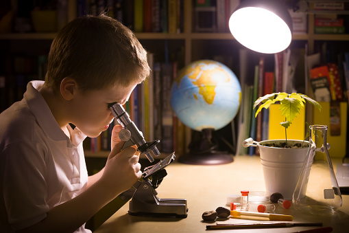 istock Close-up portrait of young student working with microscope in his room. Child and science experiments. Kid studying samples under the microscope. Preparing for science lesson. 1058909612