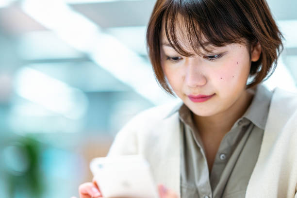 Close-up portrait of young woman while using smart phone stock photo