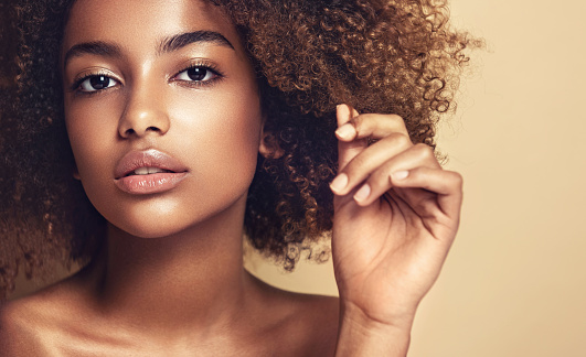 Close-up portrait of young brown skinned young woman with thoughtful and sincere look at viewer. Girl with vibrant, melanin-rich skin tone and natural Afro hairstyle. Beauty of youth.