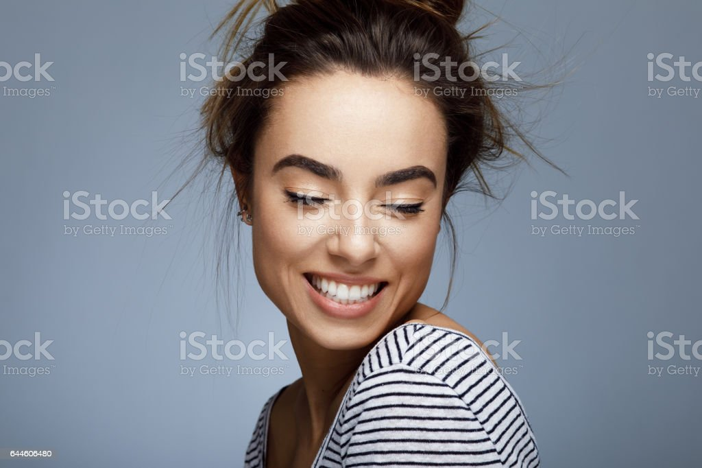 Closeup portrait of young woman with toothy smile stock photo