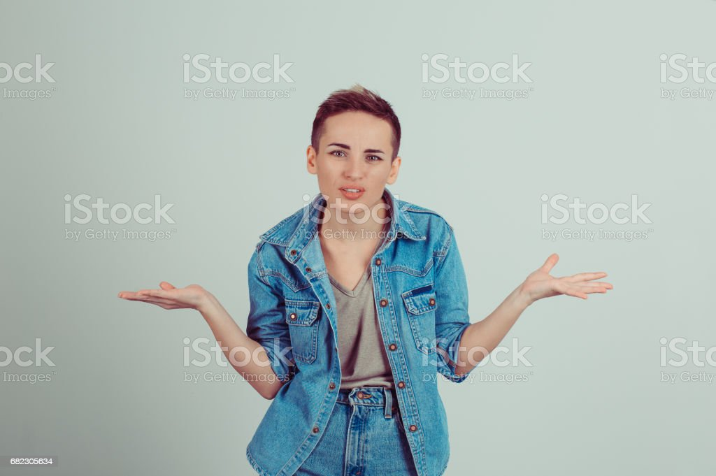 Closeup portrait puzzled clueless young woman with arms out asking what is problem who cares so what I don'u2019t know isolated grey background. Negative human emotion face expression reaction perception stock photo