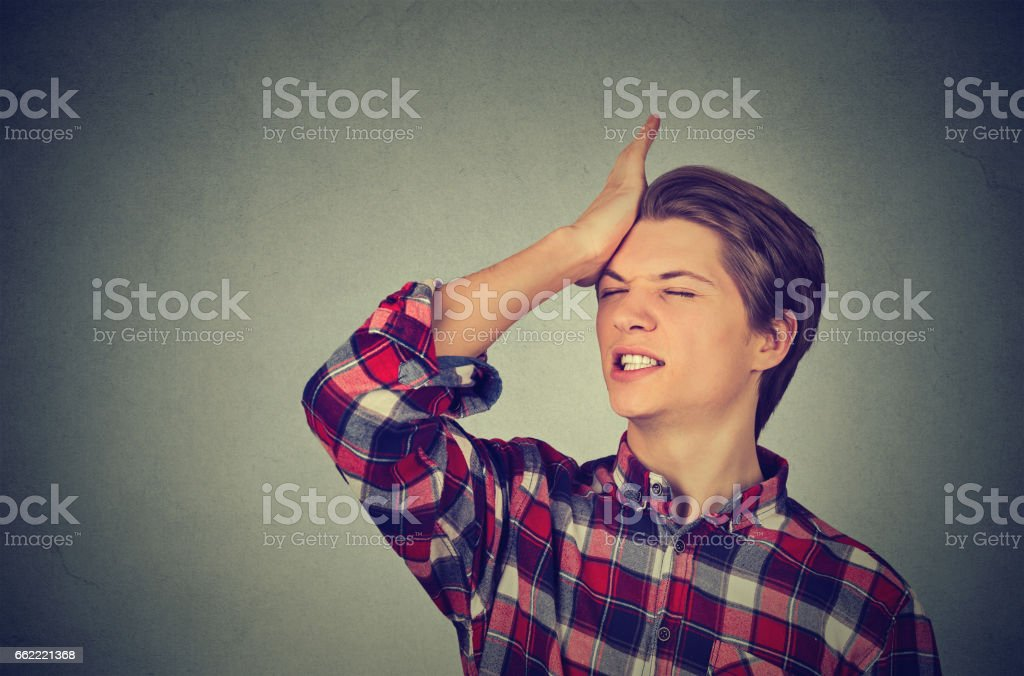 Closeup portrait silly young man, slapping hand on head stock photo