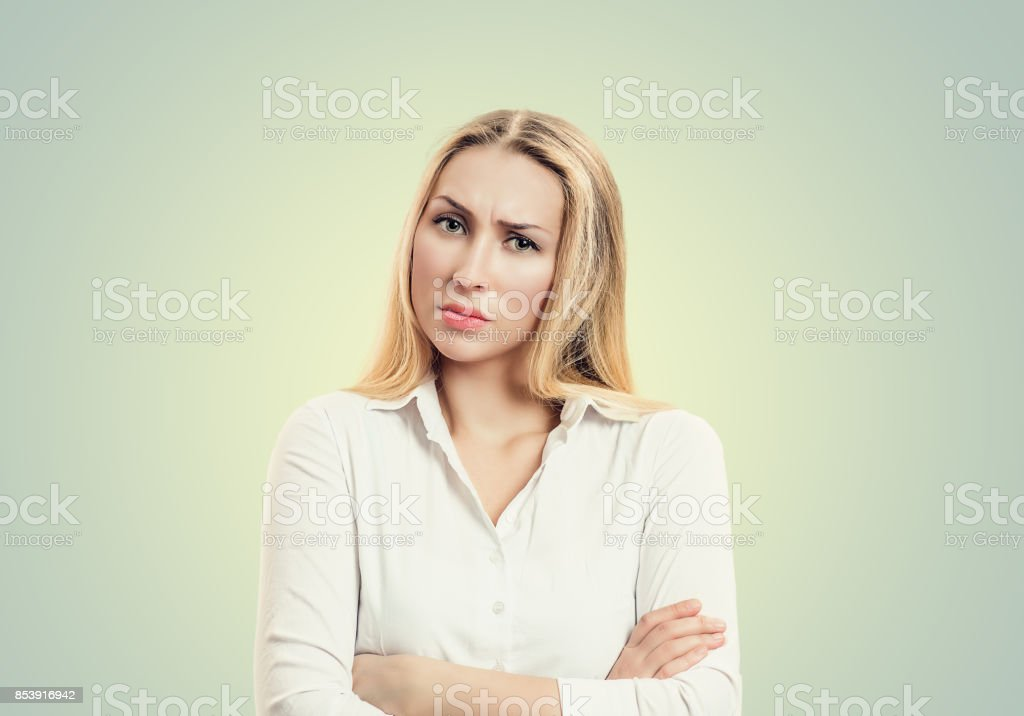 Closeup portrait, skeptical, serious senior young woman looking suspicious, disapproval on face, arms crossed folded, isolated white background. Negative human emotion, facial expressions, feelings stock photo