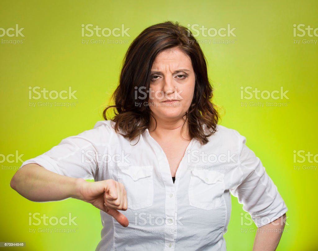 Closeup portrait unhappy, angry, mad, pissed off woman, giving thumb down hand gesture with hand looking with negative facial expression, stock photo