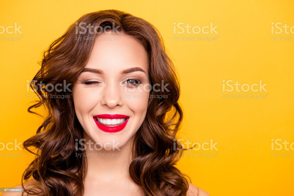 Closeup portrait with copy space empty place of pretty trendy girl with beaming smile red pomade modern hairdo winking with one eye isolated on yellow background stock photo