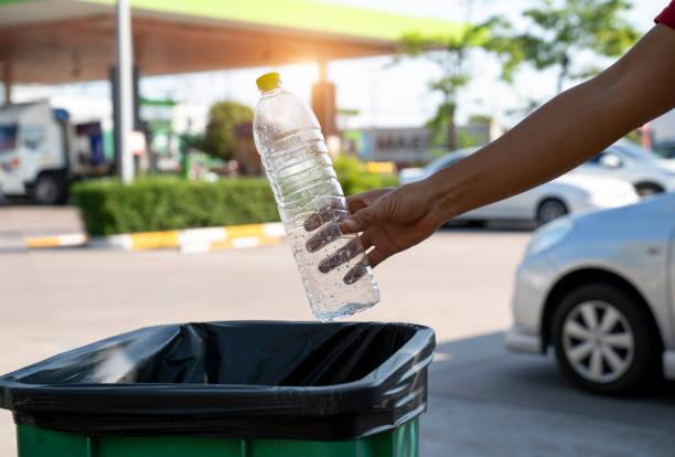 Closeup portrait woman hand throwing empty plastic water bottle in recycling bin. stock photo