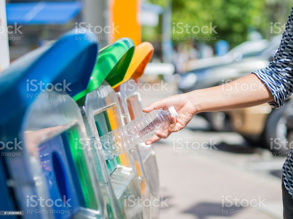 Closeup portrait woman hand throwing empty plastic water bottle in recycling bin. stock photo