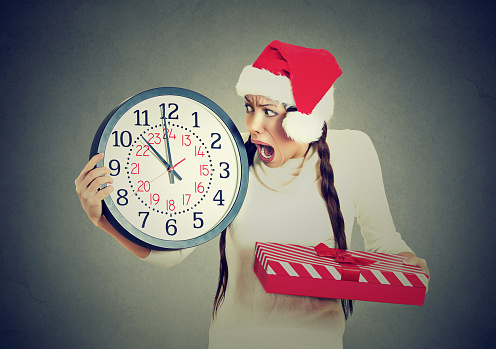 Closeup portrait worried stressed in a hurry young woman wearing red santa claus hat holding clock gift box