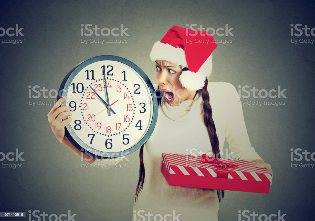 Closeup portrait worried stressed in a hurry young woman wearing red santa claus hat holding clock gift box stock photo