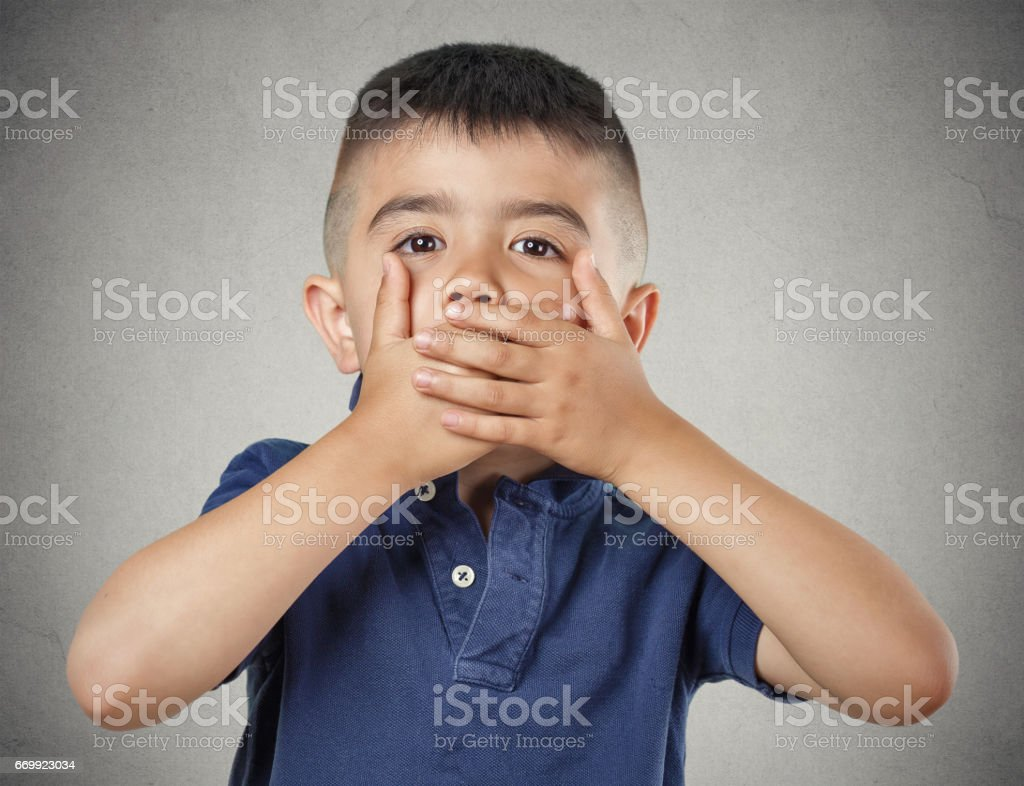 Closeup portrait young handsome man, boy closing, covering mouth with hands can't speak hiding stock photo