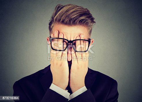 istock Closeup portrait young man in glasses covering face eyes with both hands isolated on gray wall background 873216364