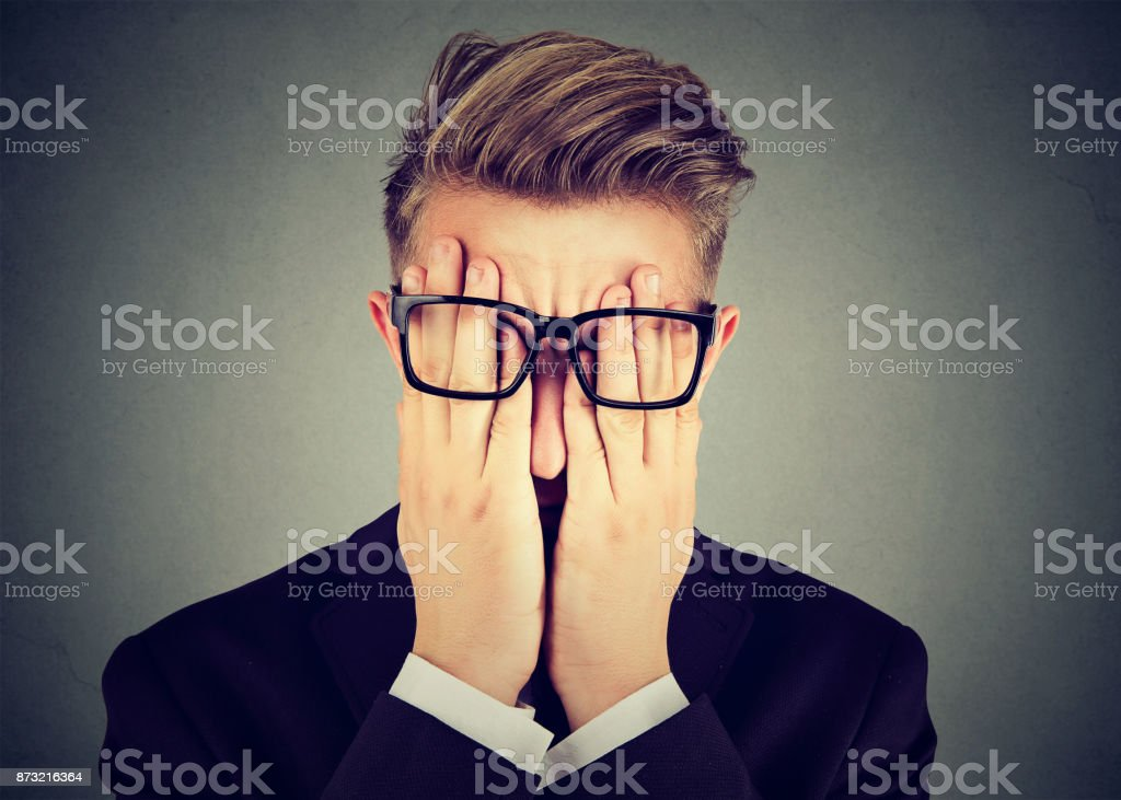 Closeup portrait young man in glasses covering face eyes with both hands isolated on gray wall background stock photo