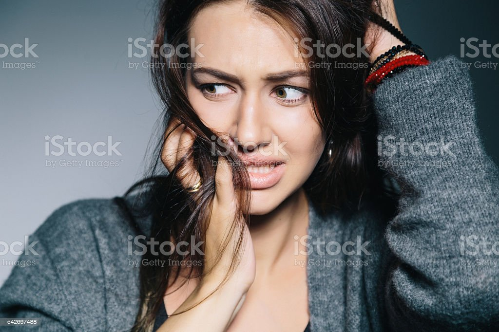 Closeup portrait young unsure hesitant nervous, isolated on gray background. stock photo